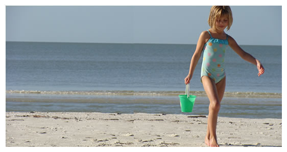 Young girl playing with sand bucket on beach